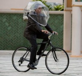 Guy on a bike with a buggy cover over his head to keep off the rain